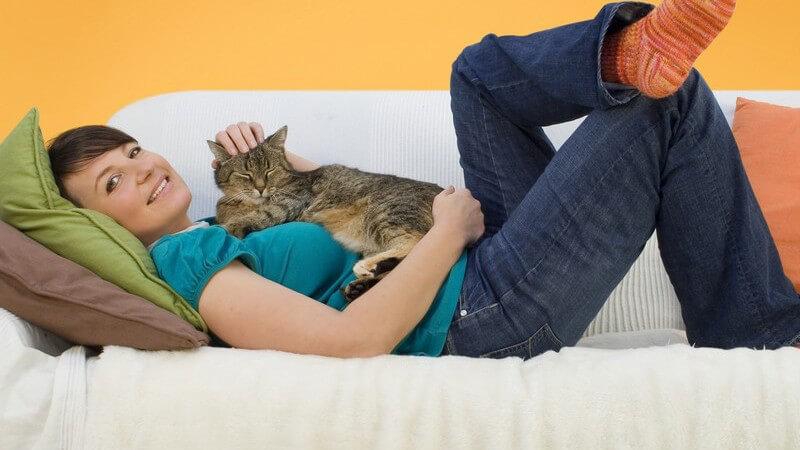 Junge Frau mit Katze auf dem Bauch liegt auf weißem Sofa mit grünem und braunen Kissen