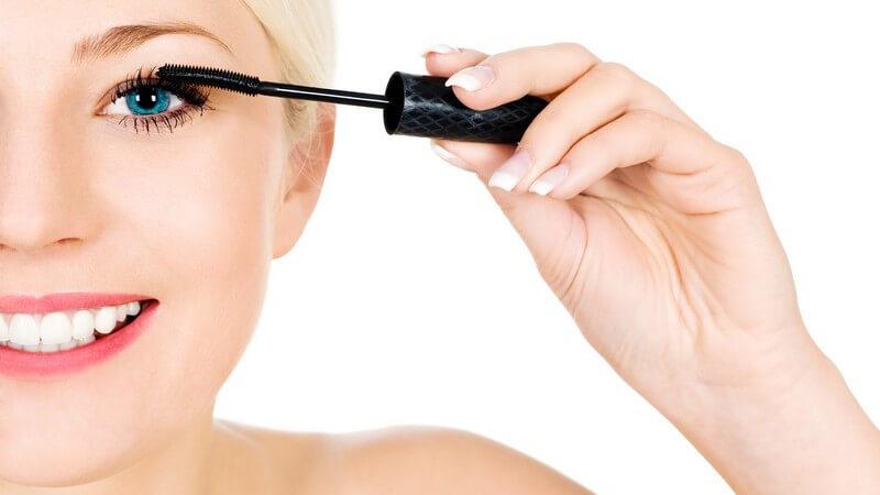 Junge blonde Frau trägt Mascara auf, weißer Hintergrund