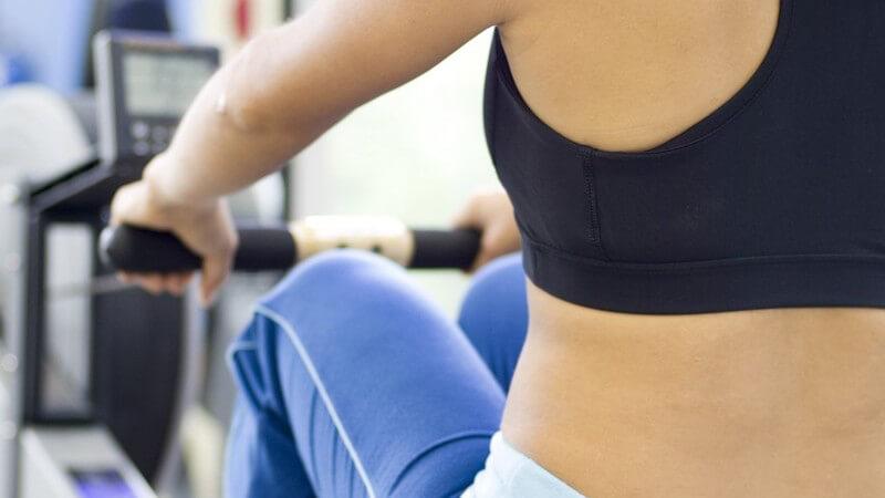 Frau mit blauer Sporthose und dunklem Top am Rudergerät im Fitness-Studio