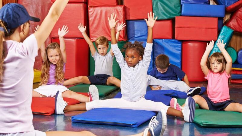 Kinder machen Gymnastik in einer Sporthalle voller roter, blauer und grüner Turnmatten, vorne die Trainerin mit Basecap