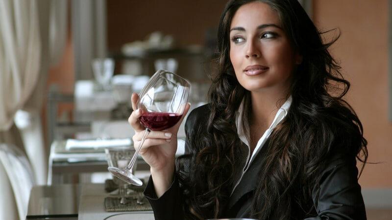 Frau sitzt mit Glas Rotwein im Restaurant und schaut zum Fenster raus