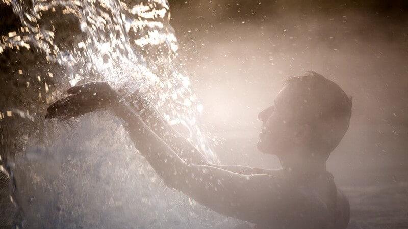 Frau badet unter einem Wasserfall im Thermalbad, verdeckt von Gischt und Nebel
