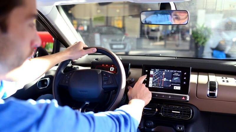 Mann sitzt am Steuer eines Autos und bedient das Navigationsgerät
