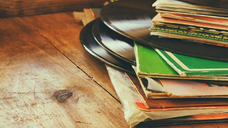 Alte Schallplatten und -hüllen auf rustikalem Holztisch