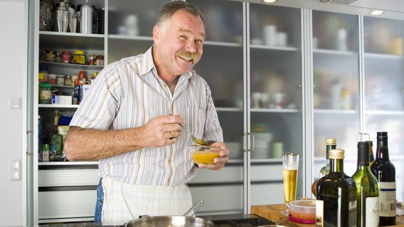 Mann mit blondem Schnurrbart rührt in der Küche, lächelt in die Kamera