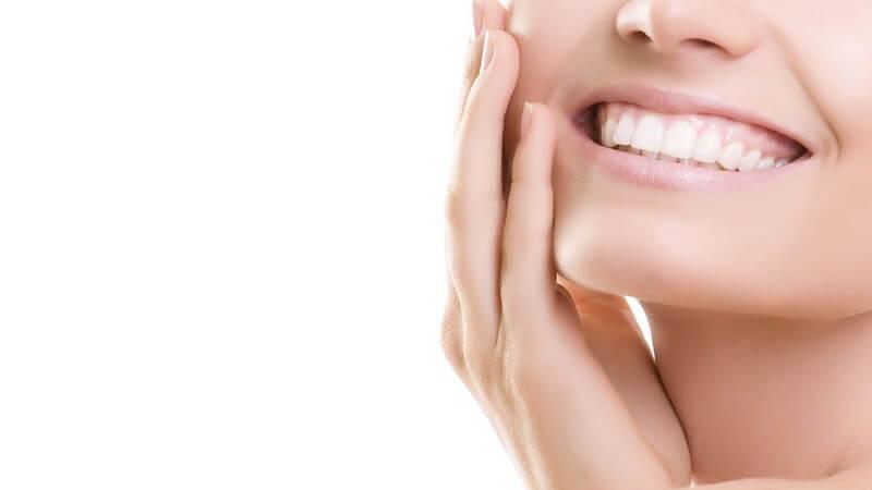 Untere Gesichtshälfte einer jungen Frau, lächelnd mit weißen Zähnen, rechte Hand an der Wange, vor weißem Hintergrund