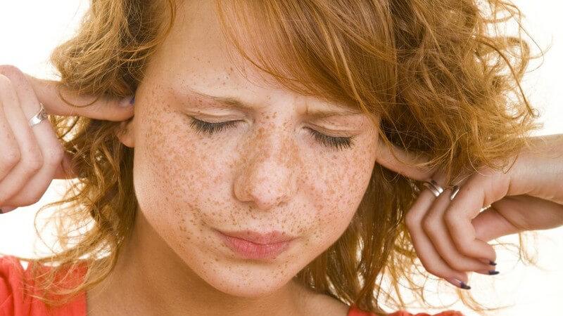 Rothaarige Frau mit geschlossenen Augen hält sich mit den Zeigefingern die Ohren zu