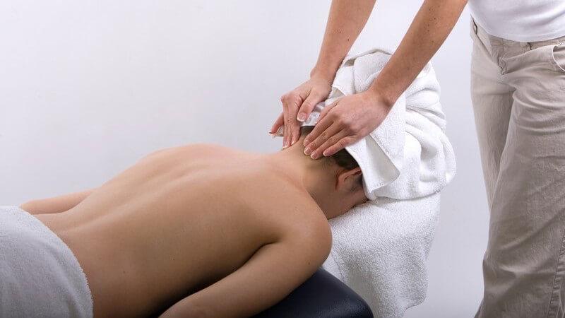 Frau liegt auf Bauch, bekommt Nackenmassage
