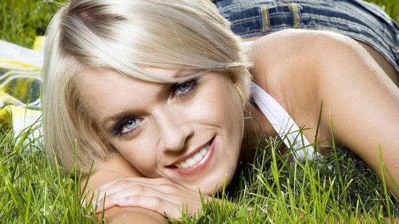 Junge Frau im Jeansrock liegt auf Wiese und lächelt in Kamera