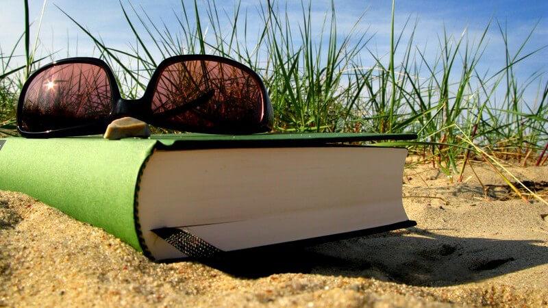 Nahaufnahme Sonnenbrille auf zugeklapptem Buch