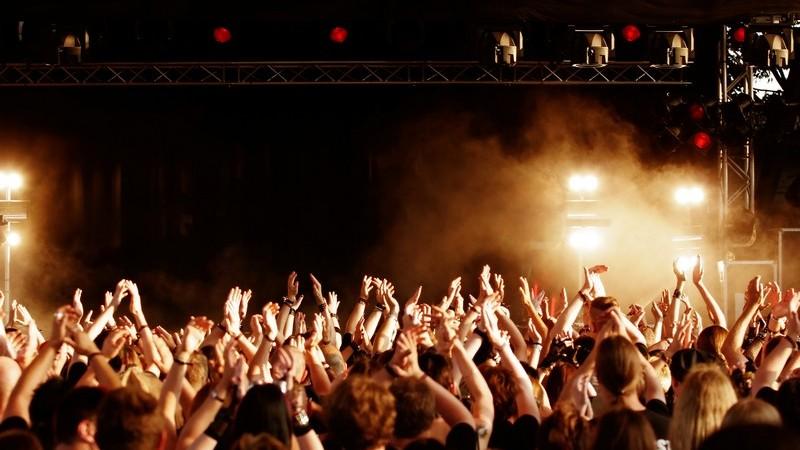 Großes Publikum auf Open Air Konzert vor Bühne mit Nebel
