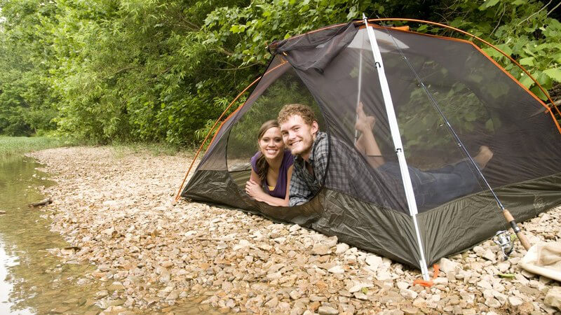 Junges Paar beim Zelten, Zelt steht am Flussufer auf Steinen