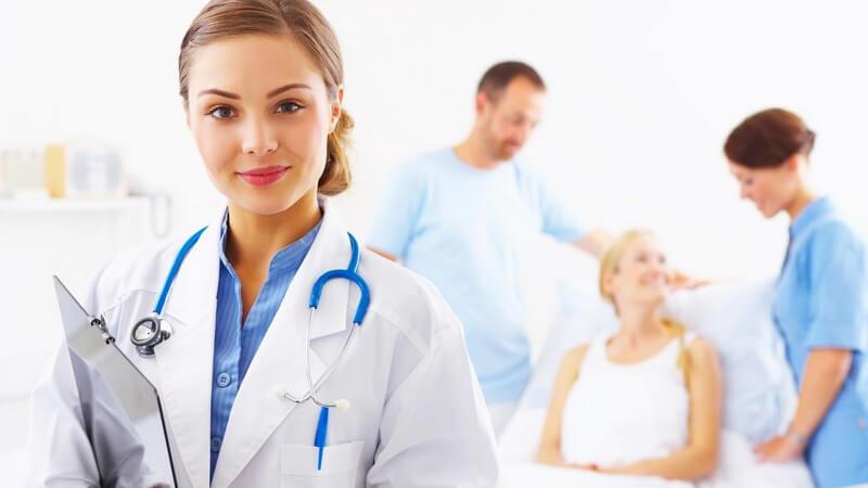 Junge Ärztin im Vordergrund, Patientin mit Freund und Krankenschwester im Hintergrund
