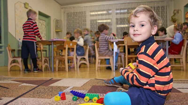 Kindergarten, Junge sitzt auf Teppich und spielt
