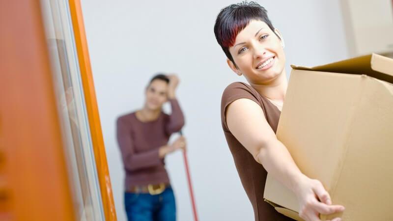Junge Frau trägt Umzugskarton in neuer Wohnung