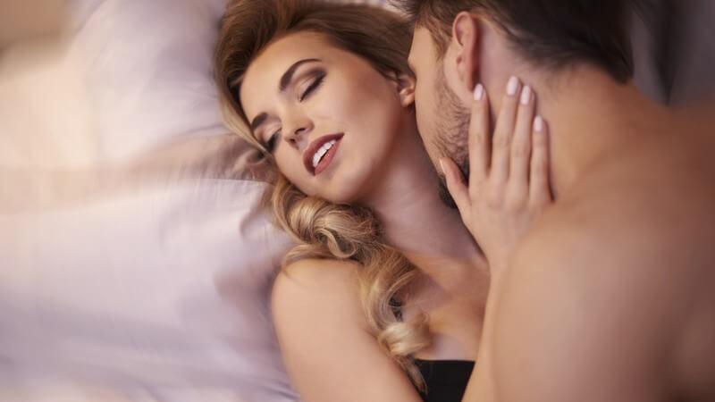 Paar beim Sex auf dem Bett, er liebkost den Hals seiner blond-gelockten Partnerin
