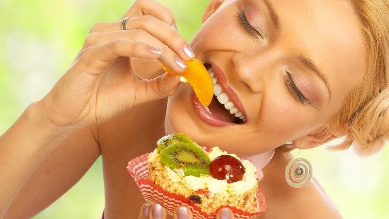 Blonde, lächelnde Frau isst mit geschlossenen Augen einen Früchtekuchen