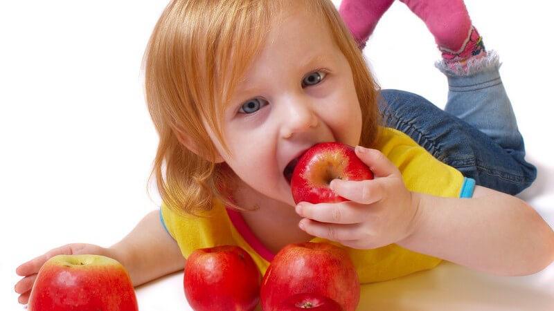 Kleines rothaariges Mädchen liegt auf dem Bauch und beisst in roten Apfel rein