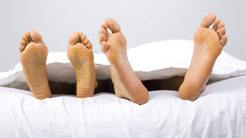 Zwei Paar nackte Füße schauen unter einer weißen Decke hervor