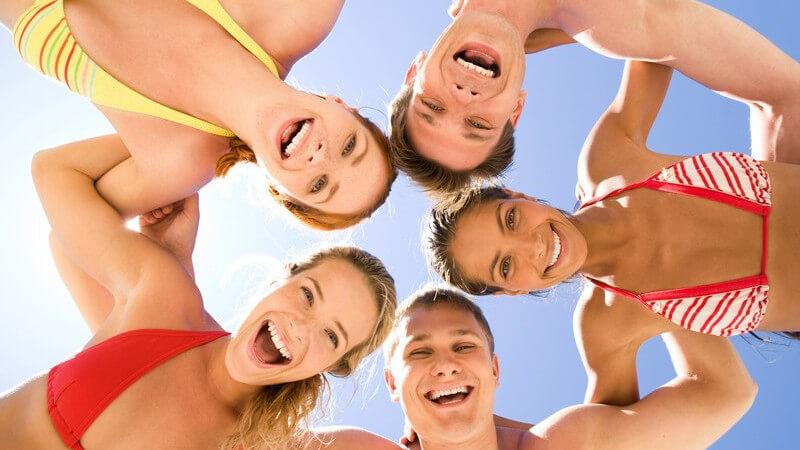 Fünf Jugendliche in Badekleidung (Bikini Badehose) stehen im Kreis und blicken nach unten in die Kamera, Sonne, Fröhlich