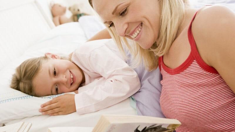 Mutter liest kleiner Tochter Gute-Nacht-Geschichte vor, beide lachen