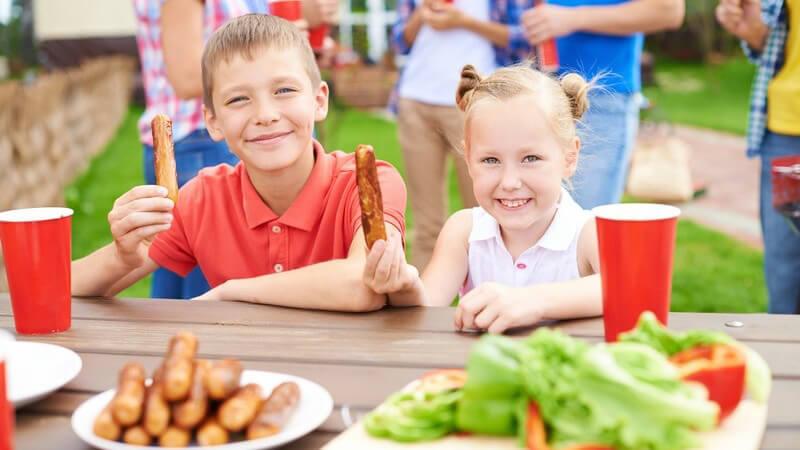 Grillen im Garten - Grillparty im Sommer, Kinder mit Bratwurst, im Hintergrund Erwachsene mit Bechern