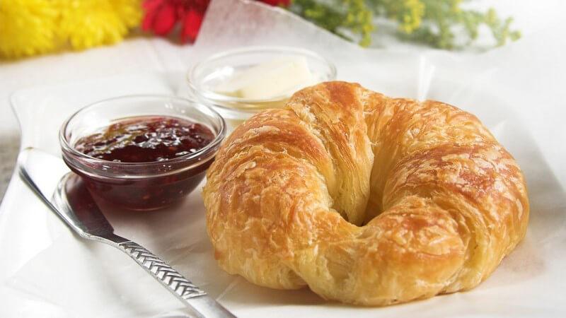 Frühstückstablett mit Croissant, Schälchen mit Marmelade und Quark, Messer, im Hintergrund Blumen