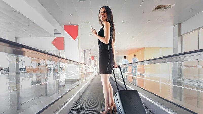 Junge Frau in engem schwarzem Kleid mit Smartphone und kleinem Rollkoffer auf einer Rolltreppe