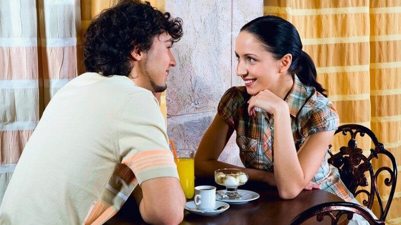 Schwarzhaariges Paar an Bistrotisch mit Kaffee, Dessert und Orangensaft