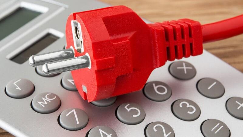 Roter Stromstecker auf silbernem Taschenrechner