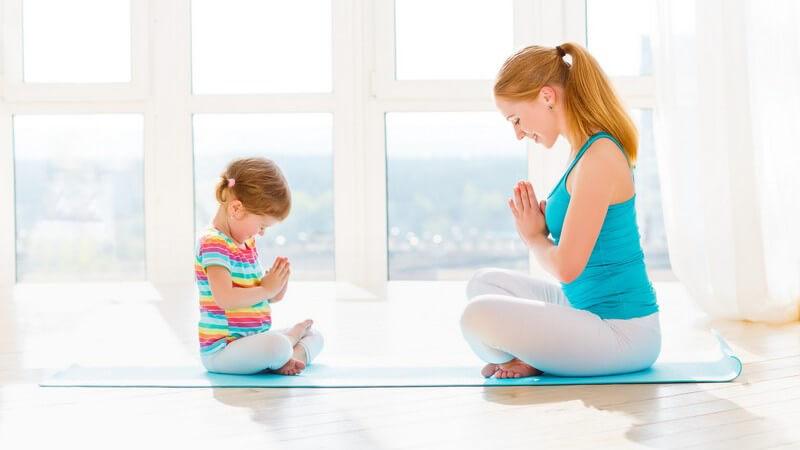 Mutter und kleine Tochter sitzten sich auf einer blauen Yogamatte gegenüber und meditieren