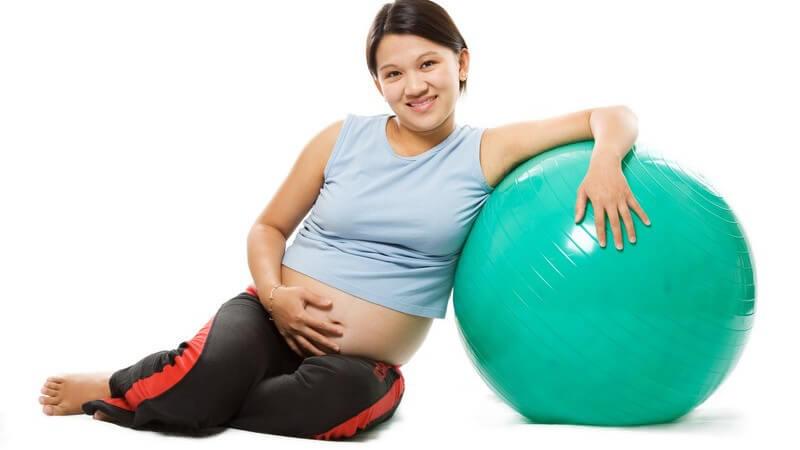 Asiatische, schwangere Frau mit Babybauch in Sportkleidung lehnt an türkisem Gymnastikball, Schwangerschaftsgymnastik