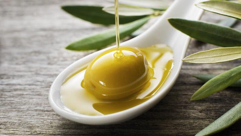 Olivenöl fließt auf eine grüne Olive auf einem weißen Löffel