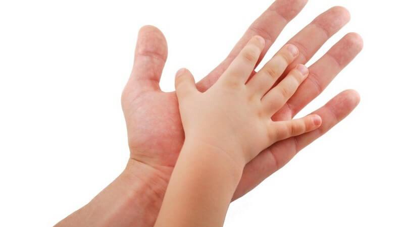 Babyhand berührt Handfläche einer Männerhand