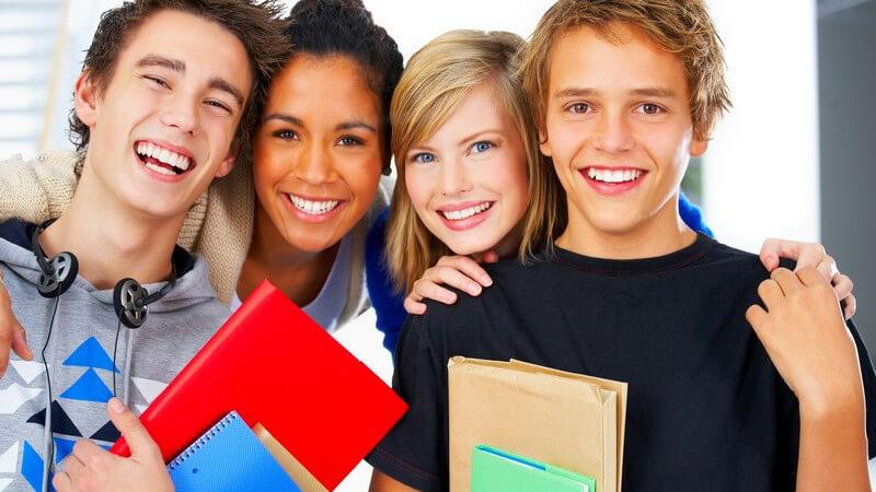 Gruppe von Schülern, zwei Jungen, zwei Mädchen, Freunde, lächelnd, mit Ringbuch und Schulbüchern unter Arm