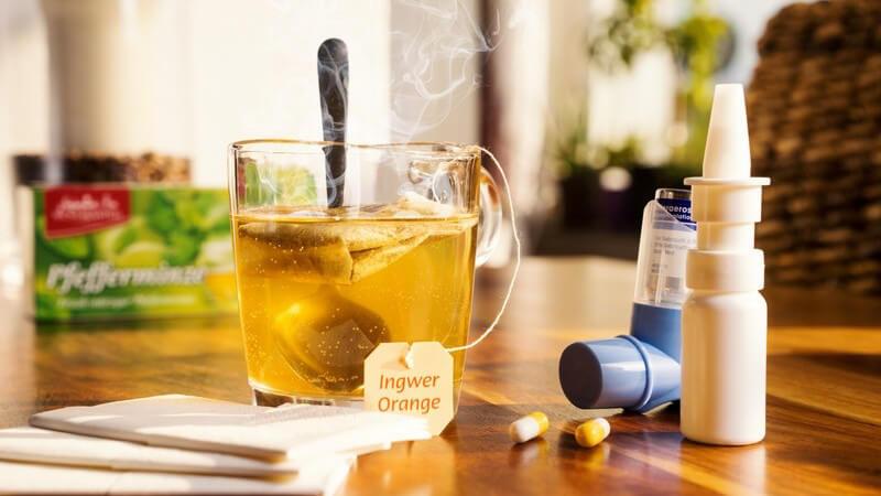 Teeglas mit dampfendem Erkältungstee neben Inhalator, Nasenspray, Tabletten und Taschentüchern