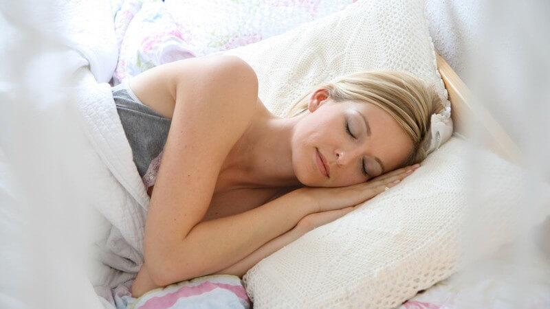 Junge Frau liegt im Bett auf der Seite und schläft