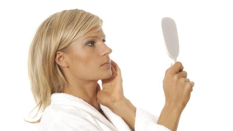 Blonde Frau im Bademantel schaut besorgt in weißen Handspiegel, eine Hand an der Wange