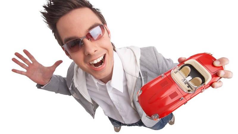 Junger, sportlicher Typ mit Sonnenbrille von oben mit rotem Modellauto