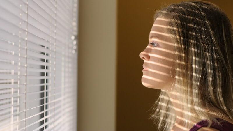 Junge Frau schaut bedrückt aus einem mit einem Plissee abgedunkelten Fenster