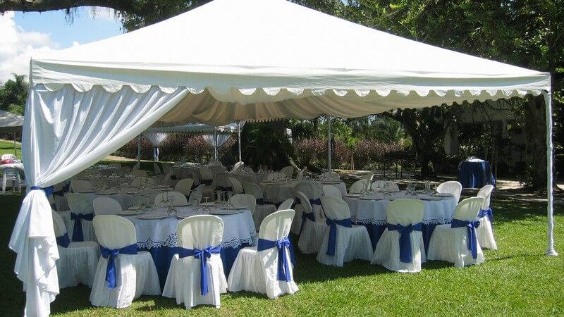 Gedeckte Tische unter weißem Zelt im Garten für Hochzeitsfeier