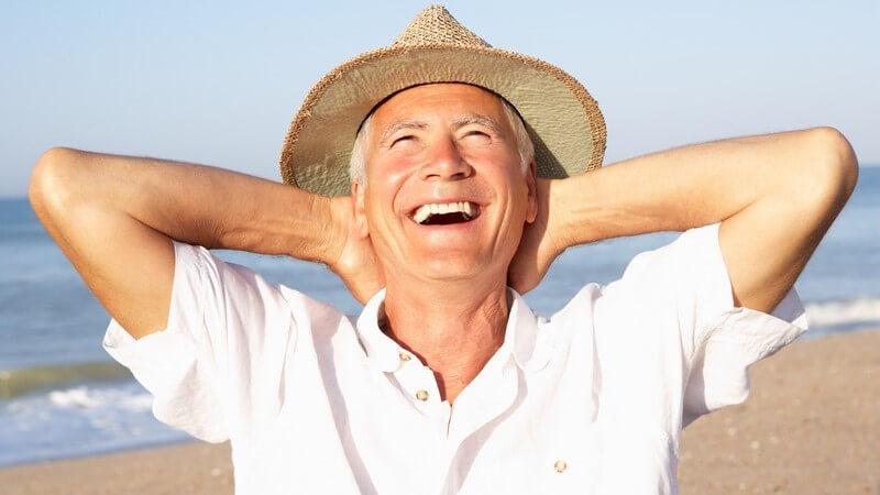 Älterer Herr mit Strohhut am Strand lacht