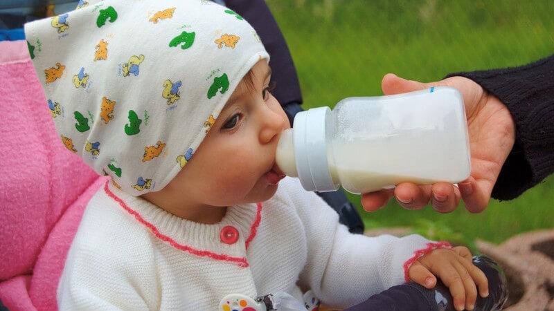 Kleinkind mit Mütze in Kinderwagen wird von Hand der Mutter mit einer Babyflasche gefüttert, im Hintergrund grüner Rasen