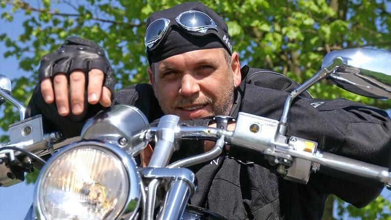 Biker mit Motorradbrille lehnt lässig über den Lenker