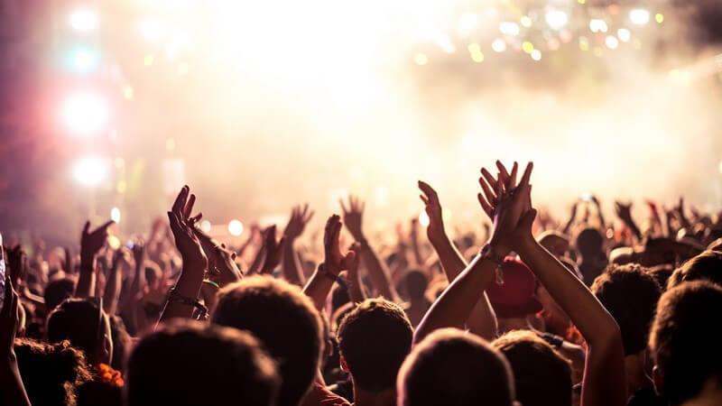 Blick über die feiernde Menschenmenge hin zur hell erleuchteten Bühne eines Konzerts