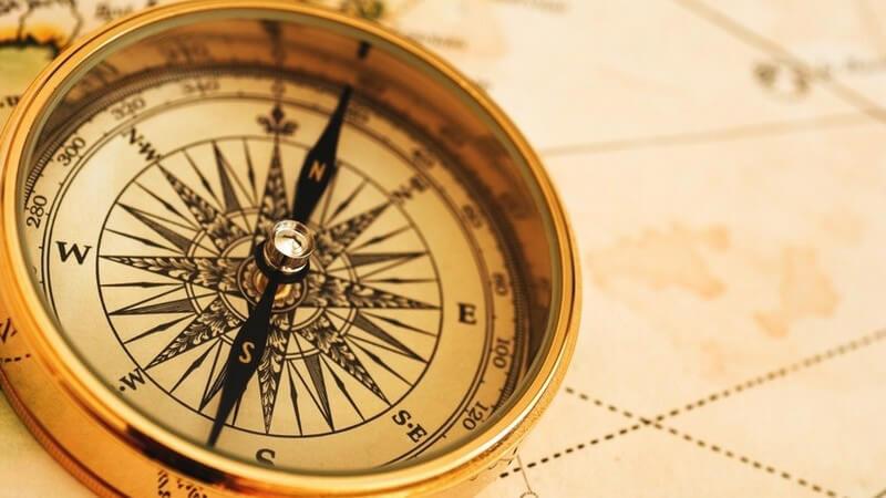 Goldener Kompass auf einer Weltkarte