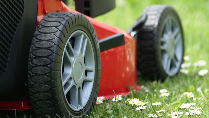 Nahaufnahme Seitenansicht roter elektrischer Rasenmäher auf Rasen