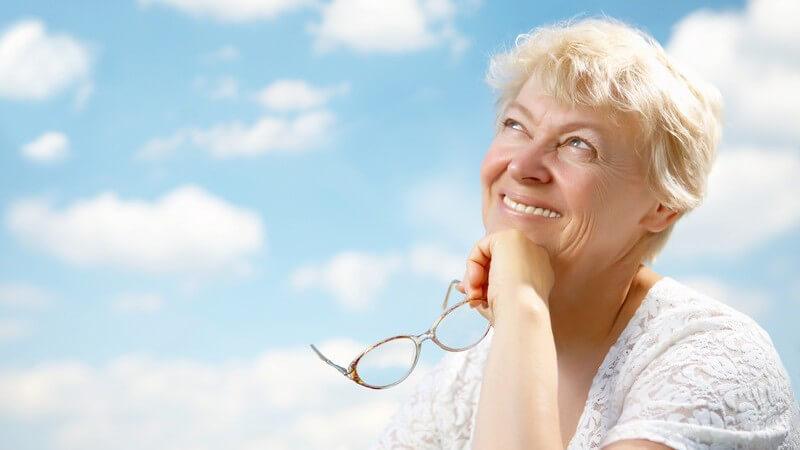 Ältere Frau mit Brille in Hand lächelt, schaut nach oben, blauer Himmel mit Wolken