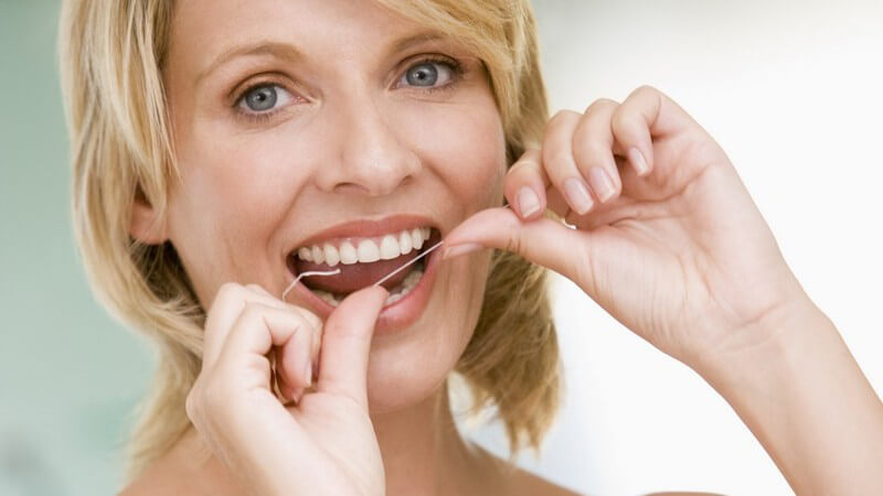 Blonde lächelnde Frau bei Mundhygiene, benutzt Zahnseide
