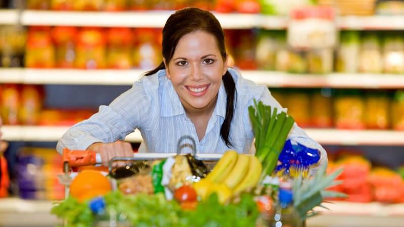Junge lächelnde Frau schiebt vollen Einkaufswagen durch Supermarkt